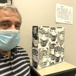 """Artist Tom Gargiulo, cofounder of the Gargiulo Arts Foundation, stands beside his multimedia installation """"Wear a Mask!"""" at the Flagler County Art League. Gargiulo will present a talk Saturday, Sept. 19, at the venue. (© FlaglerLive)"""