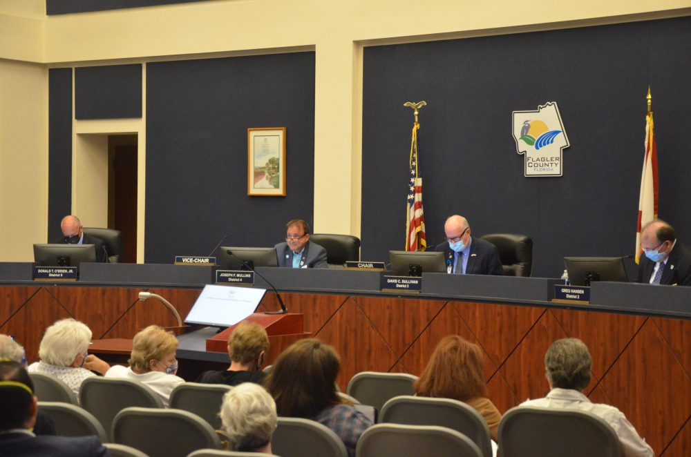 Commissioners Don O'Brien and Dave Sullivan flanked Joe Mullins Monday night. (© FlaglerLive)