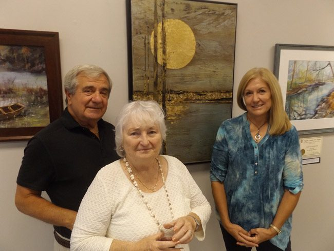 "Judi Wormeck, right, a mixed media artist and a resident of the Hammock, has been chosen as the Flagler County 2016 Artist of the Year by the Gargiulo Art Foundation. The announcement was made Saturday Oct. 15 at the Flagler County Art League by foundation co-founders Tom Gargiulo, left, and Arlene Volpe. The trio are pictured surrounding one of Wormeck's works, ""Winter Moon."" Wormeck will be honored with an exhibition of her work at Salvo Art Project in Bunnell from Jan. 21 through Feb. 13."