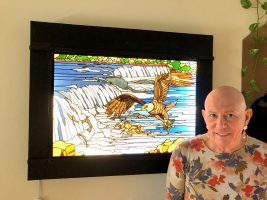 """Lee Richards with """"The Eagle at the Falls,"""" one of his stained-glass works mounted on a light box. (© FlaglerLive)"""