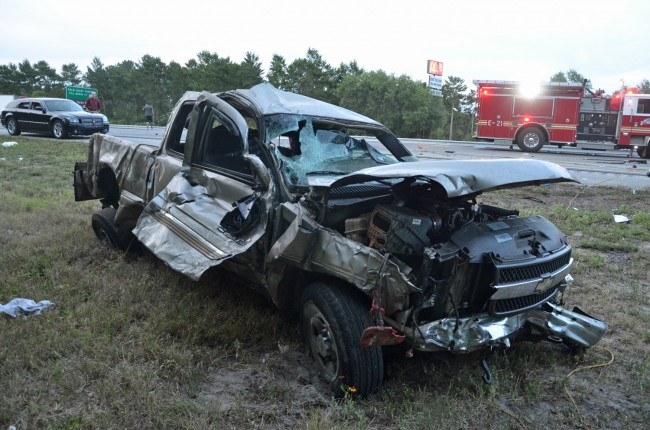 The pick-up truck jumped the guard-rail, ejecting a passenger, and crashing into a sedan. Click on the image for larger view. (© FlaglerLive)