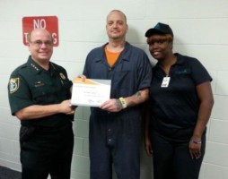 Inmate Christopher Avellar, 32, receives his food certificate of achievement as Sheriff James L. Manfre, left, and    food supervisor Paula McNeal congratulate him.