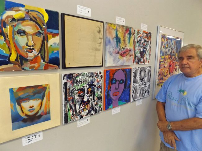 """Tom Gargiulo, one of Palm Coast's most generous art patrons and an artist in his own right,  observes the paintings created as part of the 'head' assignment during a recent workshop for area professional artists. The paintings are part of the 'Work""""'exhibit at the Flagler County Art League in Palm Coast. . Click on the image for larger view. (© FlaglerLive)"""