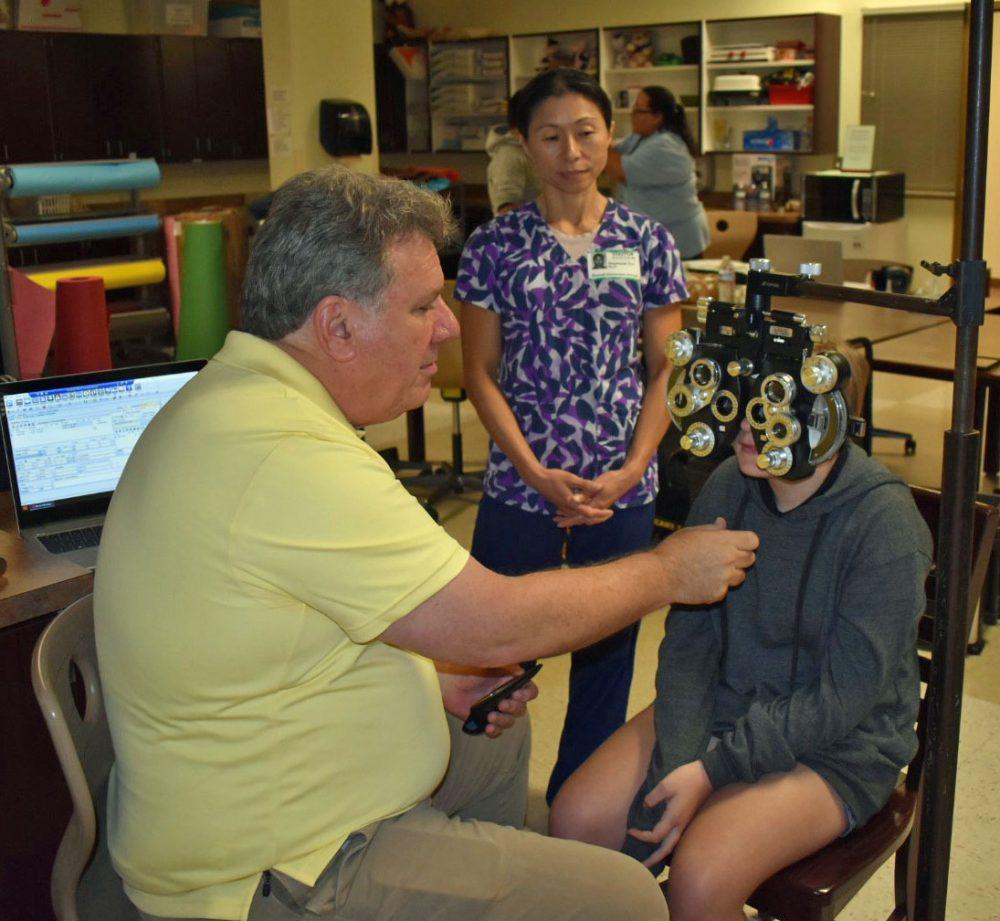RN & School Health Coordinator Stephanie Ear looks on as an optometrist from Florida Heiken screens a student.
