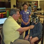 RN & School Health Coordinator Stephanie Ear looks on as an optometrist from Florida Heiken screens a student.
