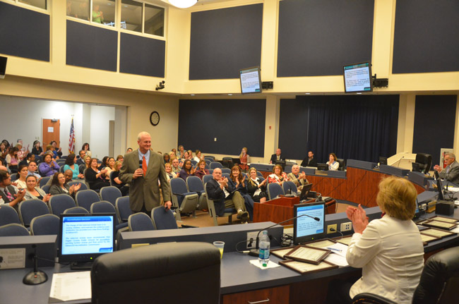 There was reason for applause today as George Griffin of AdvancEd, standing with the microphone, told the Flagler County School Board of its renewed accreditation. (© FlaglerLive)