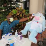 Josh, an AdventHealth Palm Coast employee, taking the temperature of a plush gift from Flagler Beach volunteers, who delivered the gifts to the hospital on April 13 as a result of efforts by resident Wanda Duff. (Wanda Duff)