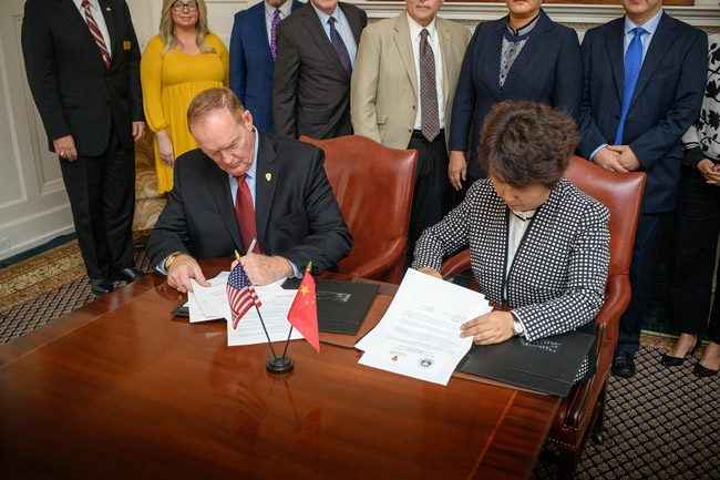 Flagler College President Joseph G. Joyner signs the agreement with CFAU Vice President LI Hongmei in the President's Board Room in Ponce de Leon Hall at Flagler College on Monday. (Flagler College)