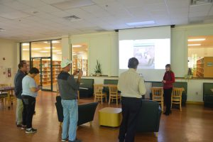 Library Director Holly Albanese today showing a series of pictures to illustrate how the homeless around the library have impacted her staff and patrons. Click on the image for larger view. (© FlaglerLive)
