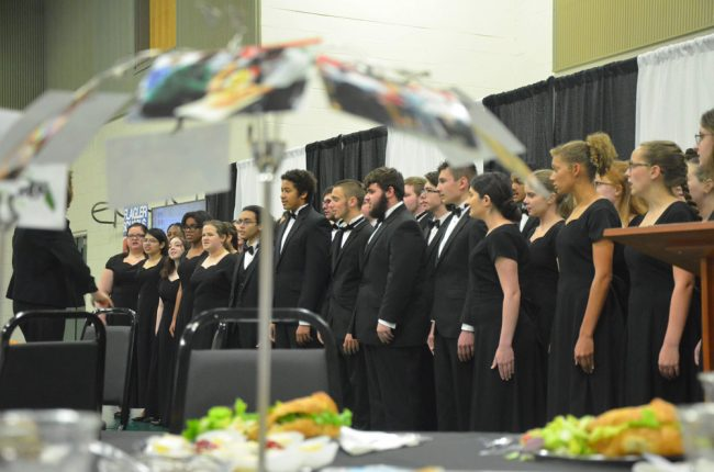 Amy Fulmer's Formality Singers opened the symposium with a performance. At every table, a parasol-like arrangement of pictures illustrated every school's flagship program. (© FlaglerLive)