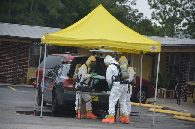 The Hazmat team analyzing samples next to a Bunnell city police cruiser in mid-afternoon. (c FlaglerLive)
