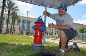 School Board Chairman Andy Dance transforming the hydrant in front of the county courthouse. Click on the image for larger view. (© FlaglerLive)