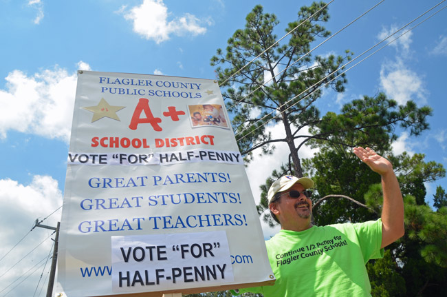 Andy Dance, the Flagler County School Board member, was the tireless point man in the effort to renew the half-cent sales tax for Flagler schools. He was waving for the cause under a midday sun at the intersection of Belle Terre and Palm Coast Parkway today. (© FlaglerLive)