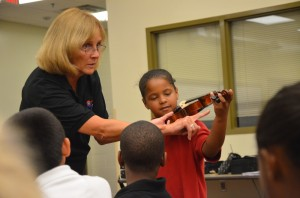 Angelina Descartes gets her first touch of a violin with Sue Cryan at Rymfire Elementary. Click on the image for larger view. (© FlaglerLive)