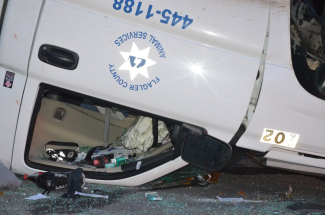 The victim at the wheel of the Humane Society truck was partially ejected. Click on the image for larger view. (© FlaglerLive)
