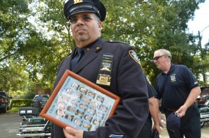 Retired New York City cop Anselmo Santoni clutched a framed montage of the 23 New York City cops killed on 9/11. An additional 37 Port Authority cops were also killed. Click on the image for larger view. (© FlaglerLive)
