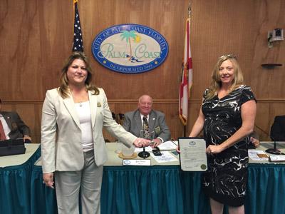 Palm Coast Urban Forester Carol Mini, right, presents the Tree City USA 10-Year Award to Palm Coast Council Member Heidi Shipley and Mayor Jon Netts.
