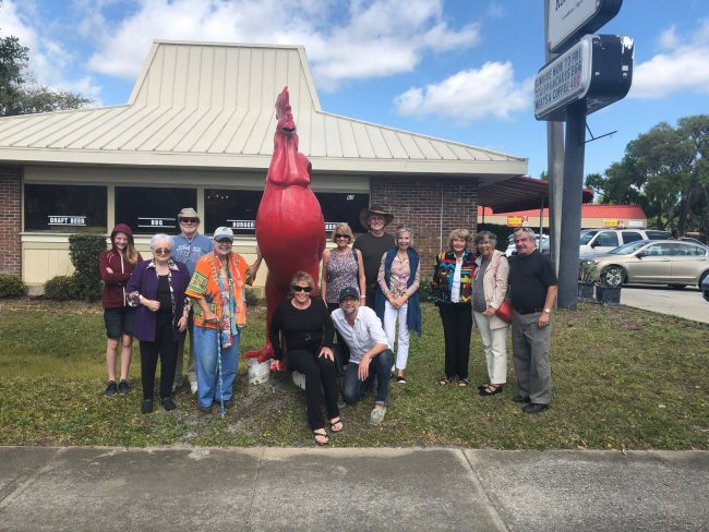 After today's ceremony all the artists headed to the Chicken Pantry in Bunnell, then posed for this shot by the red rooster, another kind of public art. (© JJ Graham for FlaglerLive)
