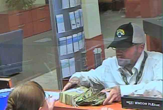 The bank robber taking possession of a wad of cash at Ormond Beach's SunTrust bank Friday afternoon.