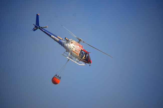 Fire Flight, the county's emergency helicopter, with its Bambi Bucket fighting a fire in 2015. (© FlaglerLive)
