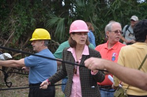 A hard-hatted, and curiously color-coordinated, Commissioner Barbara Revels, moments before the tear-down of the billboard. Click on the image for larger view. (© FlaglerLive)