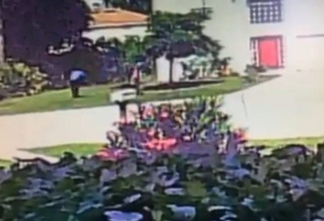 A still from a video shot by a neighbor capturing one of the two boys about to throw what appears to be a BB gun into the bushes. See the video below. (FCSO)