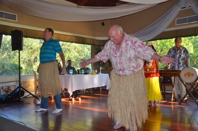 Palm Coast Fire Chief Mike Beadle, left, and Mayor Jon Netts, impressing Hawaiian gods at Sunday's fund-raiser for the Flagler Auditorium's arts in education fund. Click on the image for larger view. (© FlaglerLive)