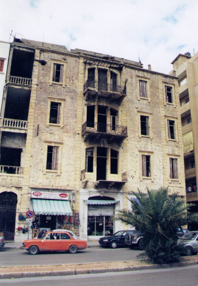 Our turn-of-the century apartment house on Beirut's Green Line in Ashrafieh. We lived on the fourth floor. My room was the second window from the right. Snipers perched atop the building, drawing fire. The round hole to the left of the floor is a direct rocket hit. Click on the image for larger view. (© FlaglerLive)