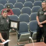 Roy Longo, center, accepting his certificates of service tonight before the Flagler County Commission after 30 years as a paramedic with Flagler County Fire Rescue, the last eight as a medic on Fire Flight, the emergency helicopter. (© FlaglerLive via Flagler County video)