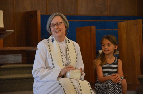 Rev. Gardner during the Children's Message segment of the service.  'When I was growing up I didn't know I was going  to be a preacher, but shere I am,' she told Mia Apfelbach, though at that moment she was looking at her son, Gregory. (© FlaglerLive)