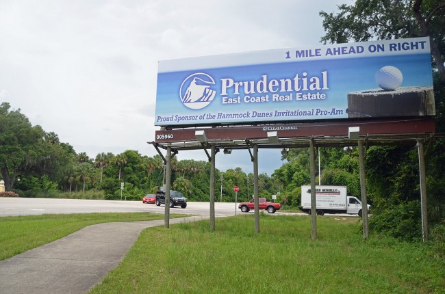 The familiar, double-sided billboard at the intersection of A1A and Camino del Mar, the road that leads to the Hammock Dunes Bridge. Click on the image for larger view. (© FlaglerLive)