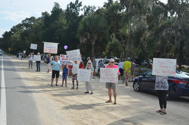 The number of protesters lining State Road A1A outside Bing's Landing Sunday fluctuated between two and three dozen. (© FlaglerLive)