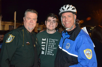 Cops embracing students: Undersheriff Jack Bisland, left, with FPC Student Government Association Tyler Perry, center, and Flagler Beach Police Chief Matt Doughney, in bike-patrol gear. (© FlaglerLive)