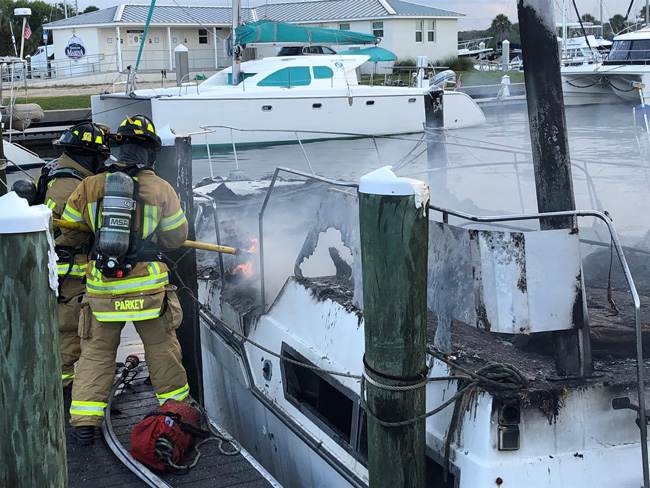 Flagler County firefighters battling the blaze on one of the two boats this afternoon in Marineland. (Flagler Professional Firefighters Firefighters)