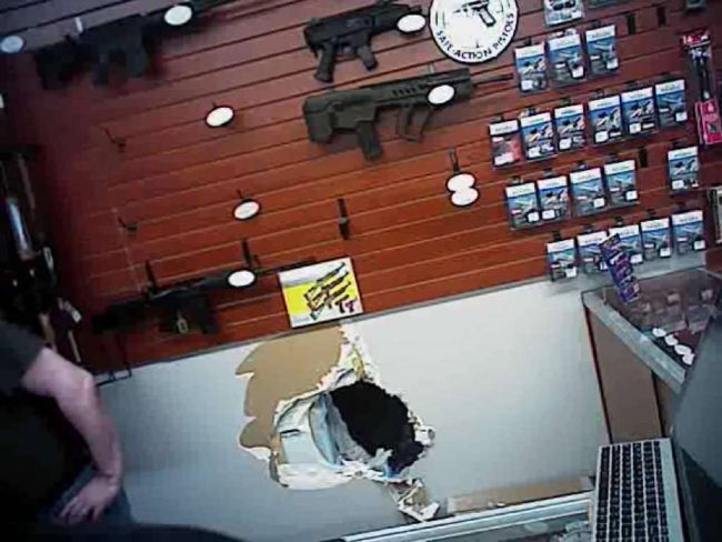 Police video footage shows a hole burglars crawled through last year to break into Grey Wolf Armory in Pasco County. (Pasco County Sheriff's Office)