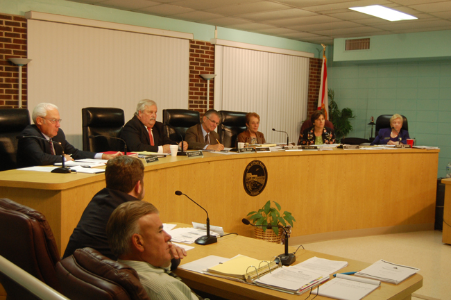 Bruce Campbell, in the foreground, is still the executive-in-waiting as the Flagler Beach City Commission ponders his fate. Drew Smith, the city's attorney, is sitting next to Campbell. On the dais, from left: Marshall Shupe, Steve Settle, John Feind, Jane Mealy, Kim Carney, and Mayor Alice Baker. (© FlaglerLive)