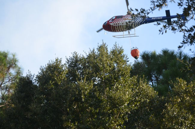 Flagler County Fire Flight was dropping water buckets on the fire this afternoon, keeping it under control until firefighters could get to it. (c FlaglerLive)