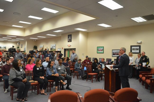 There was something surreal about the news conference setting, in a middle school library, when superimposed on its theme and subject matters. Click on the image for larger view. (© FlaglerLive)