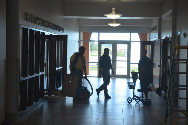 Workers outside Palm Coast government's building department as City Hall was getting ready to open in 2015. (© FlaglerLive)