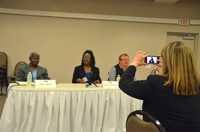 Rebecca DeLorenzo, president of the Flagler County Chamber of Commerce, takes a measure of one of the candidates just before the forum the chamber organized ahead of the March 4 elections to the Bunnell City Commission. The candidates from left: Daisy Henry, Bonita Robinson and John Rogers. (© FlaglerLive)
