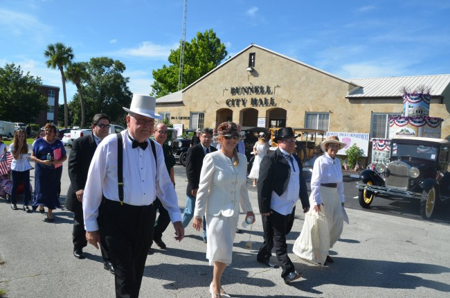 Style and sensibility: the Bunnell City commissioners  dressed the part as they made their way past vintage cars and Bunnell's victory float, toward the site of the time capsule's burial Monday. From left, Bill Baxley, Jenny Crain-Brady, John Rogers and Catherine Robinson. Elbert Ticker was there, but had to absent himself at one point. Click on the image for larger view. (© FlaglerLive)