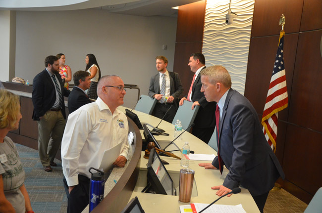Bunnell City Commissioner John Sowell, left, speaking with Rep. Paul Renner after the legislative delegation meeting at Palm Coast City Hall, while Sen. Travis Hutson, further back, speaks with School Board Chairman Trevor Tucker. (© FlaglerLive)
