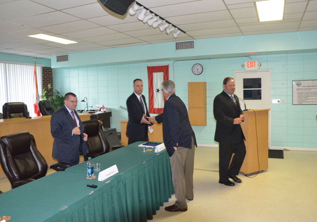 The three candidates immediately after their presentations to some 35 people who gathered at City Hall Thursday evening. From left, Joe Sisti, Matthew Doughney--shaking hands with City Manager Bruce Campbell--and Steve Clair. (c FlaglerLive)