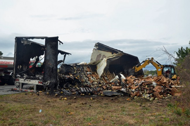 To ensure that the fire would not start again, a backhoe demolished what remained of the trailer hauling tons of cantaloupe. Click on the image for larger view. (© FlaglerLive)