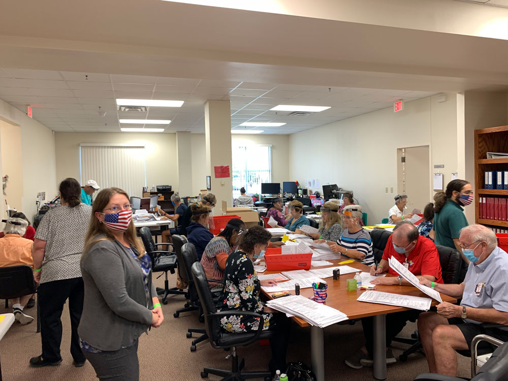 The Flagler County Canvassing Board and other elections office workers put in a full day going through mail-in ballots Wednesday. Elections Supervisor Kaiti Lenhart is in the foreground, to the left. (© FlaglerLive)