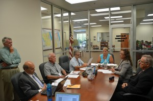 Today's Canvassing Board meeting. From left, County Attorney All Hadeed, Palm Coast City Council member Dave Ferguson (standing), County Commissioner Charlie Ericksen (an alternate member of the Canvassing Board), County Commission Chairman George Hanns, Supervisor of Elections Kimberle Weeks, County Judge Melissa Moore-Stens, whio chairs the board, and City Council member Bill McGuire. Virginia Smith, the Palm Coast City Clerk, was to the right of Ferguson. Click on the image for larger view. (© FlaglerLive)