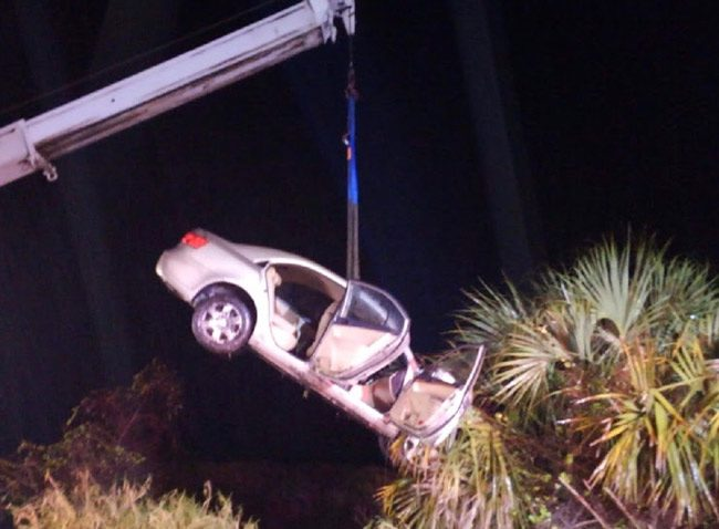 The victim's car being lifted by a crane last night: John's Towing of Bunnell pulled the car out of a 15-foot deep canal. (© FlaglerLive)