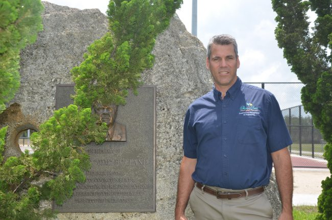 Palm Coast Construction Manager Carl Cote next to the park's namesake's plaque: both are sleeping better these days. (c FlaglerLive)