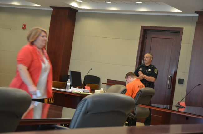 Carl Devore, seated, cried as his mother testified, and cried as she walked by him afterward, the closest she'd been to him since dropping him off at the Sheriff's Office 441 days ago, never to see him in person, or touch him, since. (c FlaglerLive)