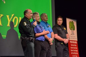 Carman and Sgt. Mike Lutz, second from left, developed an elaborate active-shooter drill into a show they put on for scores of audiences. They're seen here at one such drill for 1,000 Flagler County school faculty members last fall, with Sheriff Rick Staly and homeland security director Randall Stroud. (© FlaglerLive)